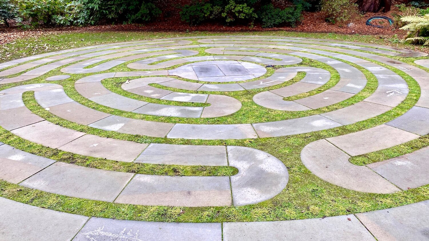 A maze made of stones wraps around the lawn creating a circular shape overall.