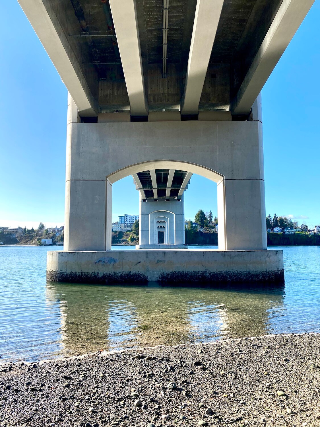 The underside of Manette Bridge, with a water view shows blue sky against the concrete support structures of the bridge that connects the oceanside community of Manette with the city of Bremerton.