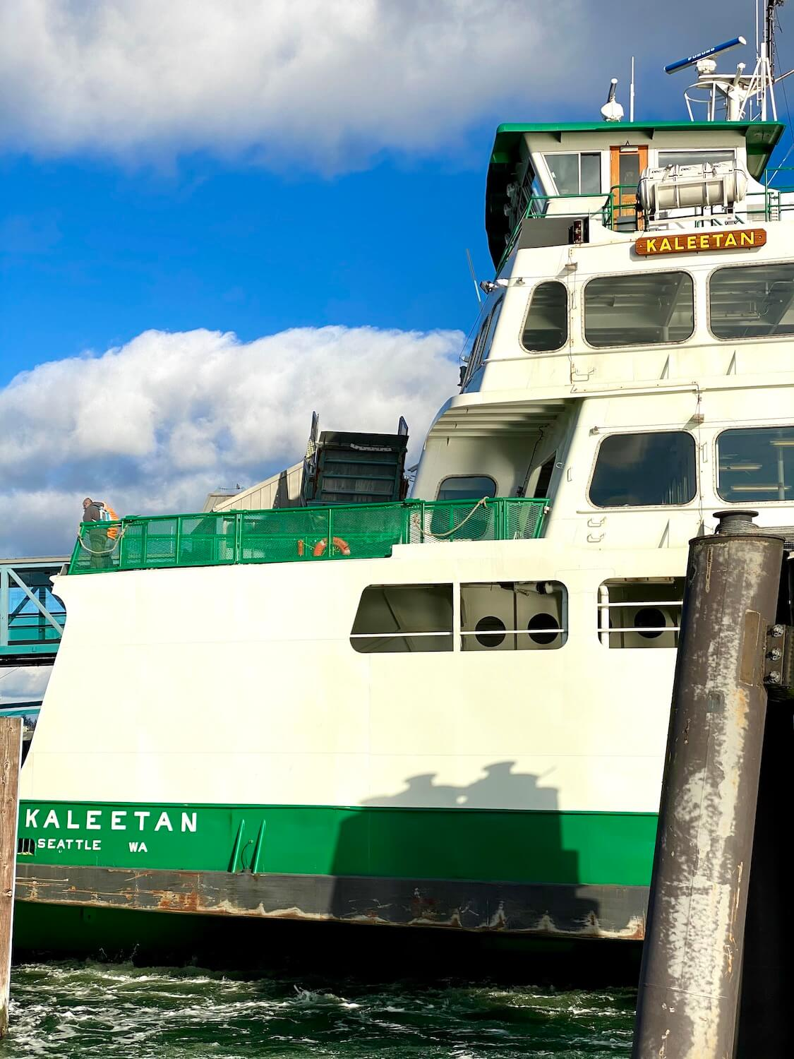 A close of photo of the ferry Kaleetan, sailing into the dock in Bremerton, Washington.  The ferry is white with green accents, including a bright green deck railing.