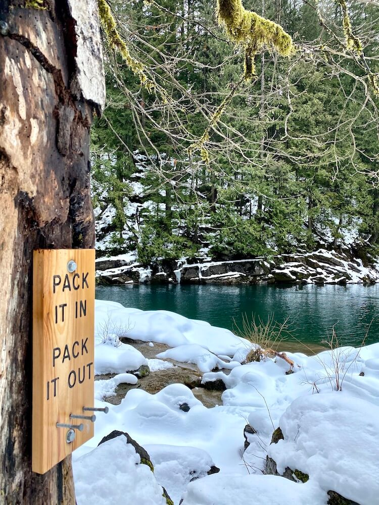 """A wooden sign made from blond wood with black carved letters says, """"Pack it in... Pack it out"""" and is nailed against a tree on the side of the road from Seattle to Leavenworth, Washington.  The river flows in the background through rocks covered with snow and young fir trees leading up the bank on the other side of the icy blue green river."""
