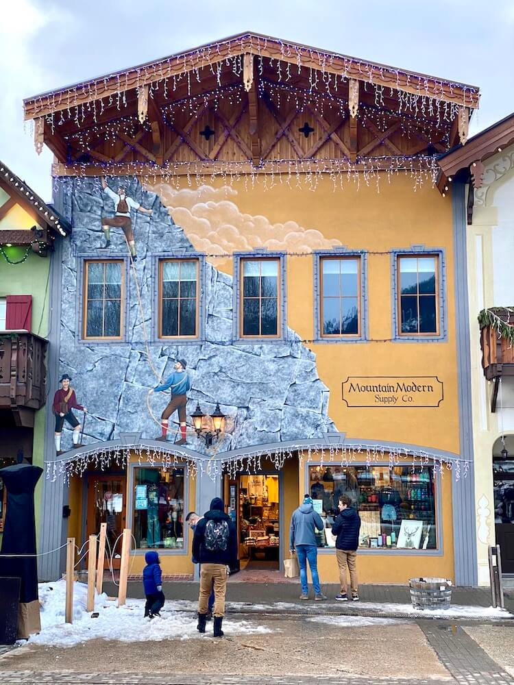 A quaint German style store front is sandwiched between other themed buildings in the downtown of Leavenworth, Washington.  On the side of the building a mural is painted that depicts Bavarian hikers climbing up the rocky side of a mountain.