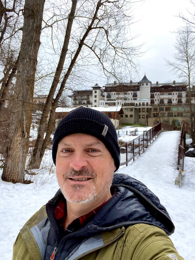 A selfie of Matthew Kessi, smiling in front of the dramatic German architecture of the newly built Posthotel on a Seattle weekend getaway to Leavenworth, Washington.