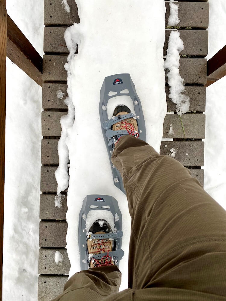 A person wearing hiking boots and snowshoes walks across a foot bridge covered in snow in this Wintry scene.  He is wearing green rain pants and enjoying this active on a Seattle weekend getaway to Leavenworth, Washington.