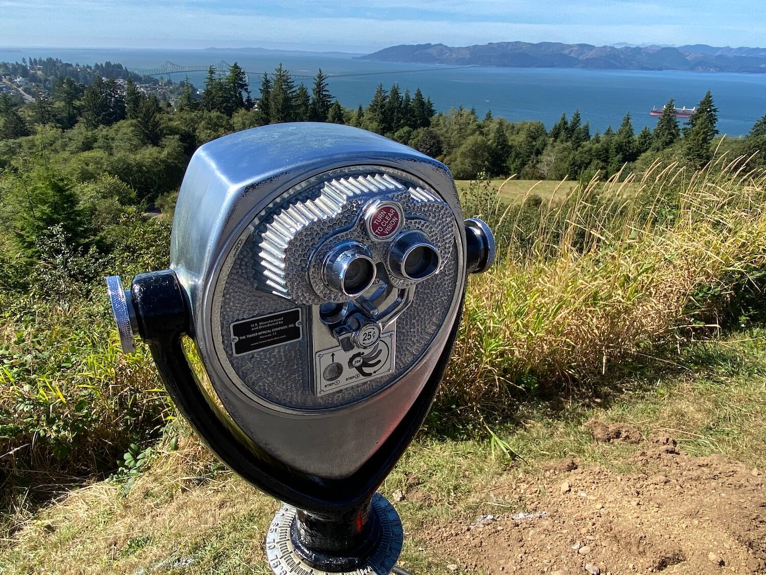 A chrome mechanical binocular will offer a closer look at the sights in the background for only 25 cents. The grass trails down to evergreen trees and eventually the waters of the Columbia River.