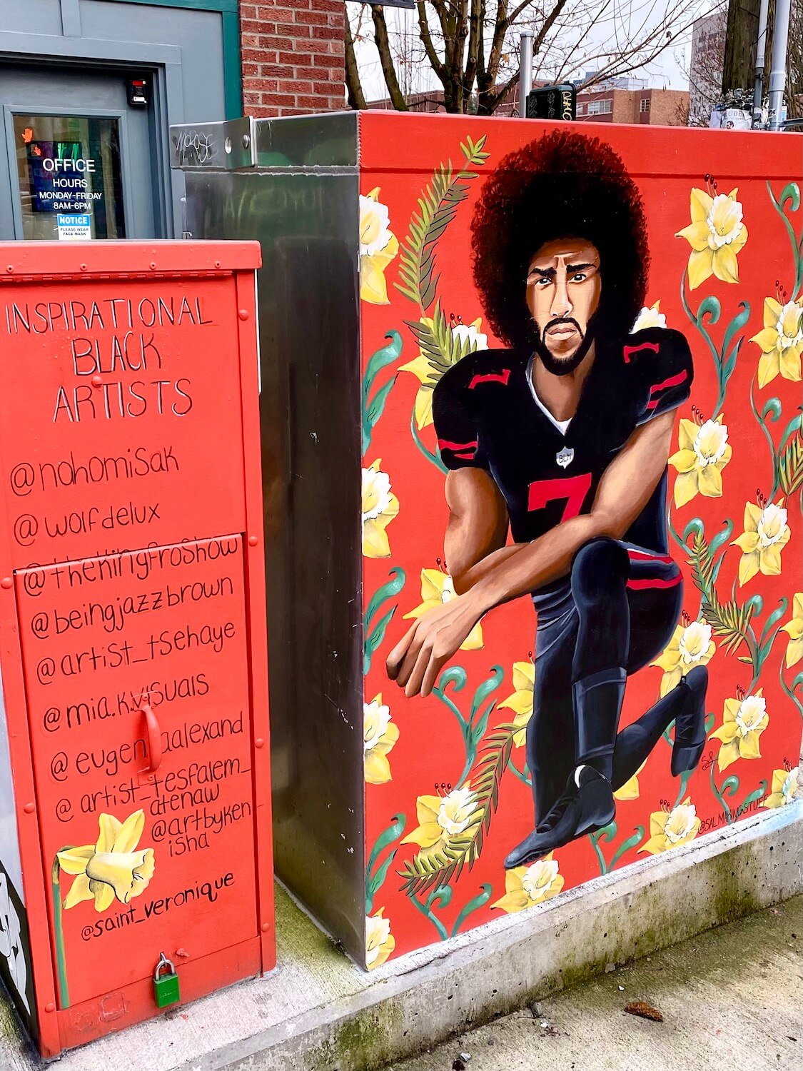 A mural of Colin Kaepernick is painted on an electrical unit and the colors are bright red background with black lettering and yellow daffodils.  The football player is wearing a black and red jersey and has his famous large black teased out hair.