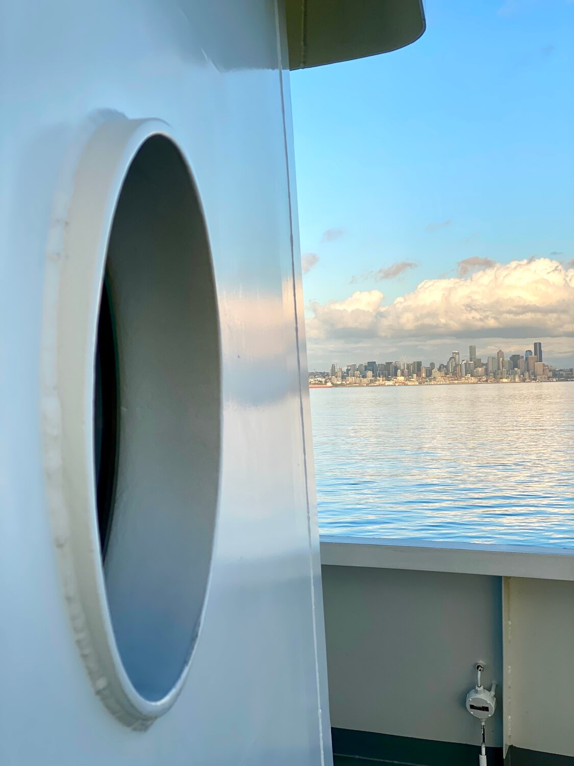 A view of the skyline of Downtown Seattle as viewed from beside a porthole on a Washington State Ferry boat traveling between Bainbridge Island and Seattle.  The water is calm and puffy clouds swim around in blue Spring skies above the city scape.