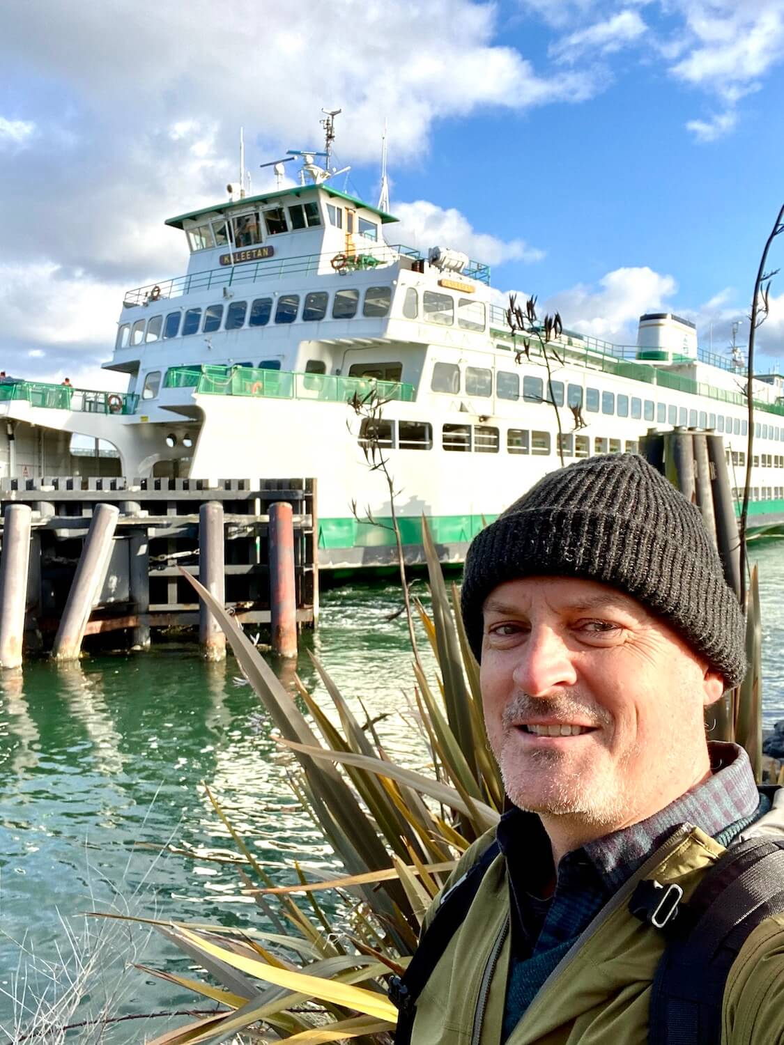 Matthew Kessi stands on the bank of the water with a Washington State Ferry in the background.  He's smiling and wearing a gray hat.  A ferry ride is a great way to spend time while on a long layover at Seatac Airport.
