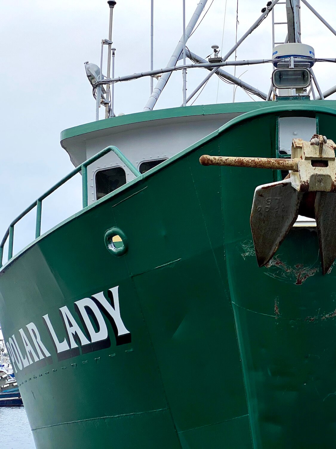 A fishing vessel named Polar Lady sits docked at Fisherman's Terminal in Seattle.  The boat is hunter green with white lettering with black shadow and a giant iron anchor is secured on the font of the vessel.