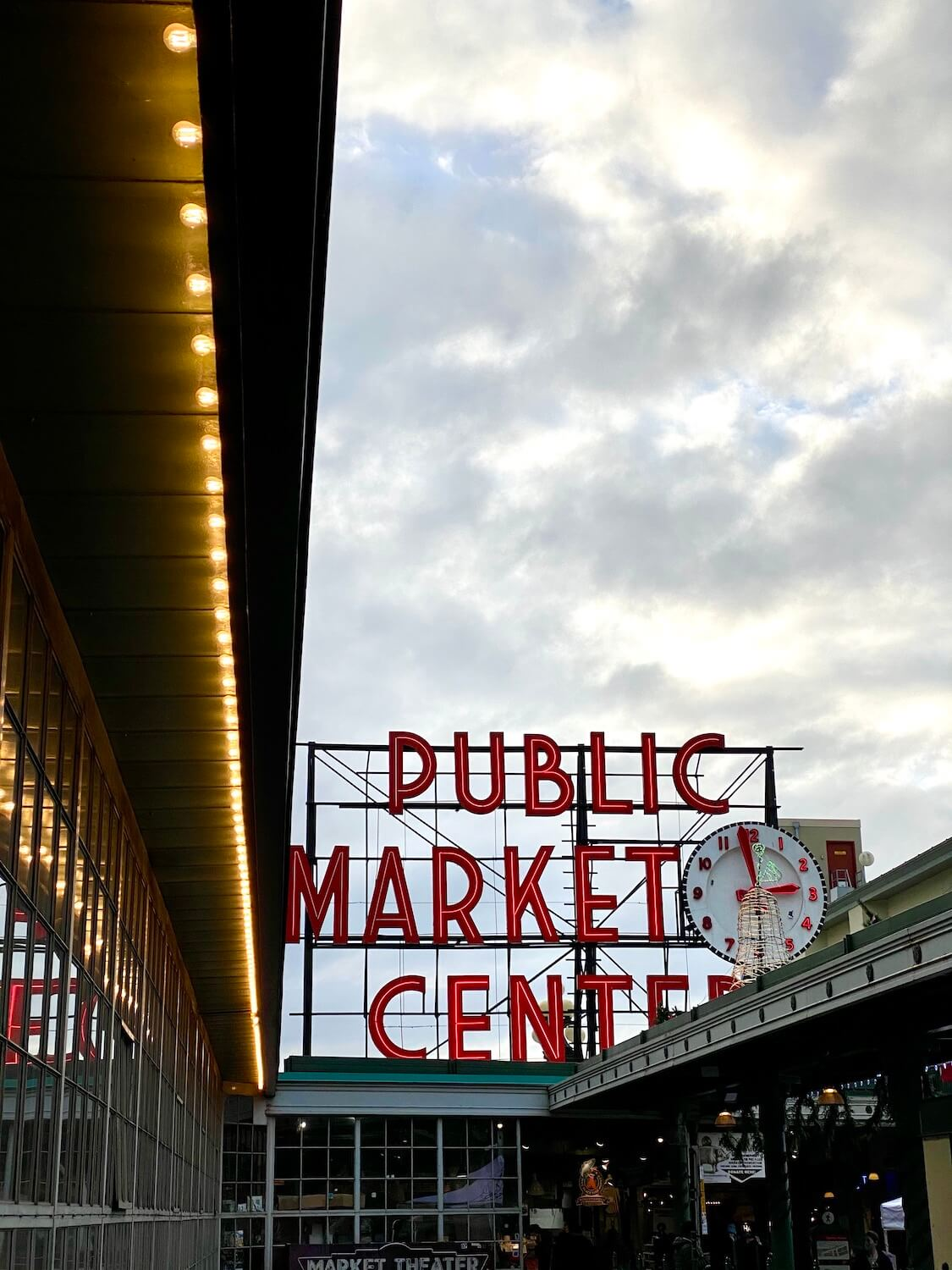 """Pike Place Market sets up a moody scene with a string of light bulbs leading to the giant red neon sign that says, """"Public Market Center.""""  The clouds are a swirl of gray above."""