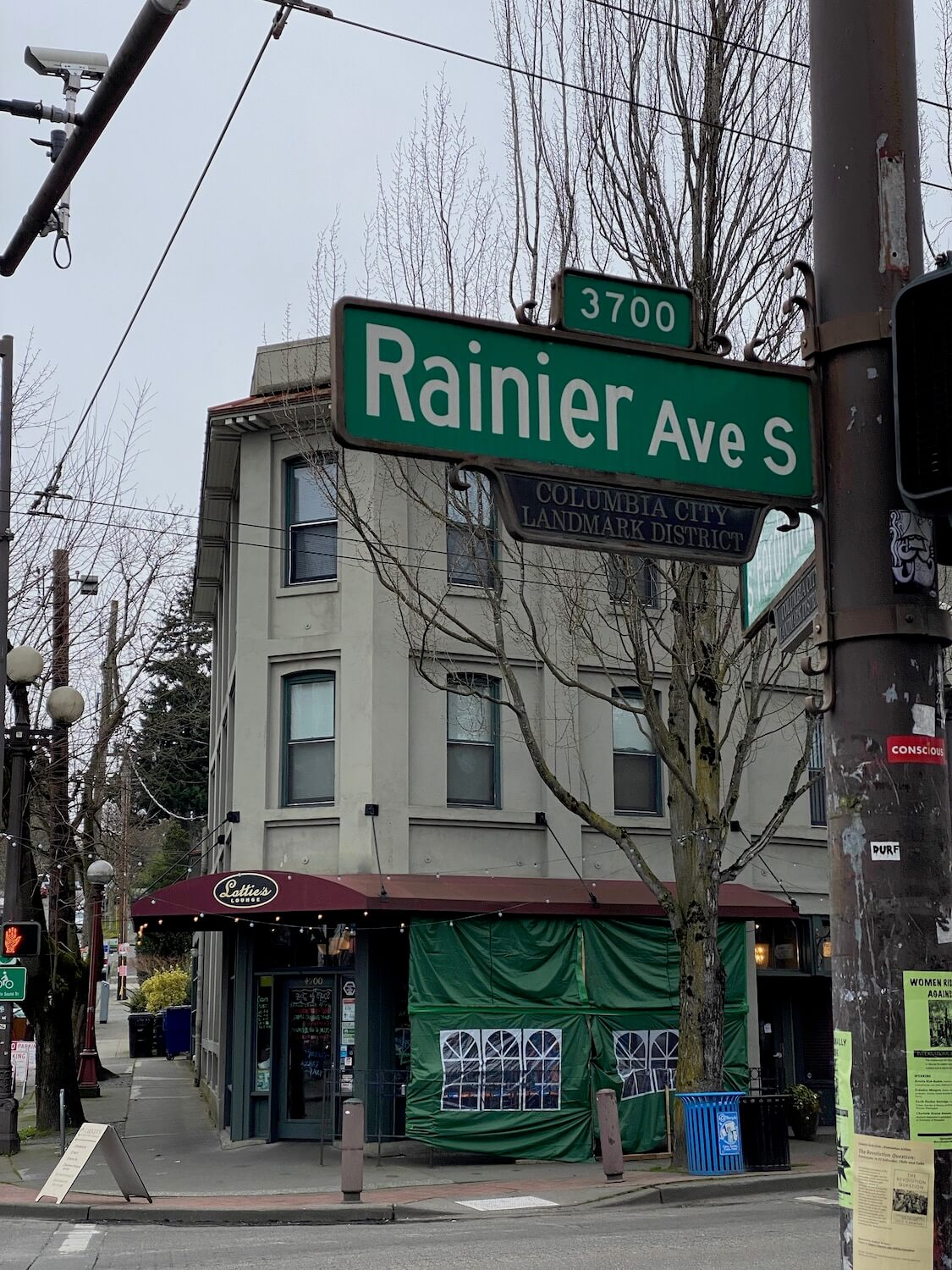 An up close photo of Rainier Ave S street sign in Columbia City district of Seattle.  In the background is a historic looking three story building and this area is a great place to spend time on a layover at Seatac Airport.