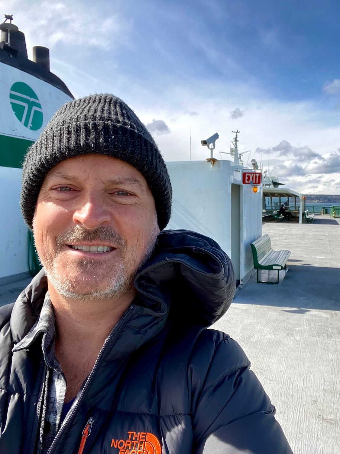 Matthew Kessi smiles while on board a Washington State Ferry, with the emblem above him from the ship's sail.  He has a scruffy gray beard and is wearing a thick wool cap.  The wide open top deck of the boat is in the background.