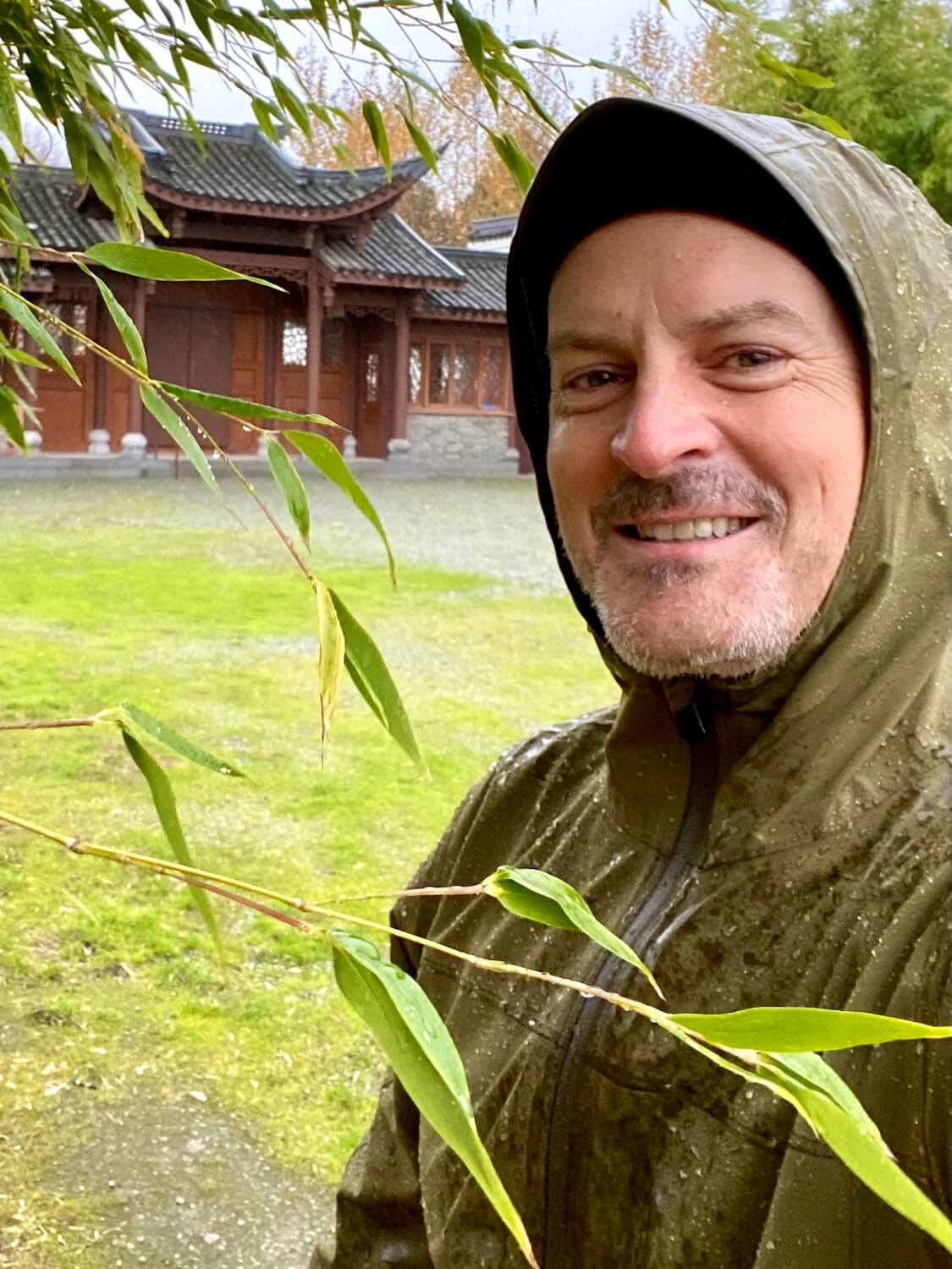 Selfie of Matthew Kessi standing amongst some bamboo plants in the rain. There is green grass and a Chinese temple in the background.