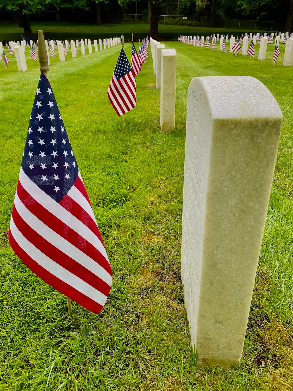 Cream colored marble grave markers are lined up in the hundreds at this military cemetery in Seattle.  For the Memorial Day celebration, each market has a crisp American flag placed upright in front of the stones on a neatly mowed field of green grass.