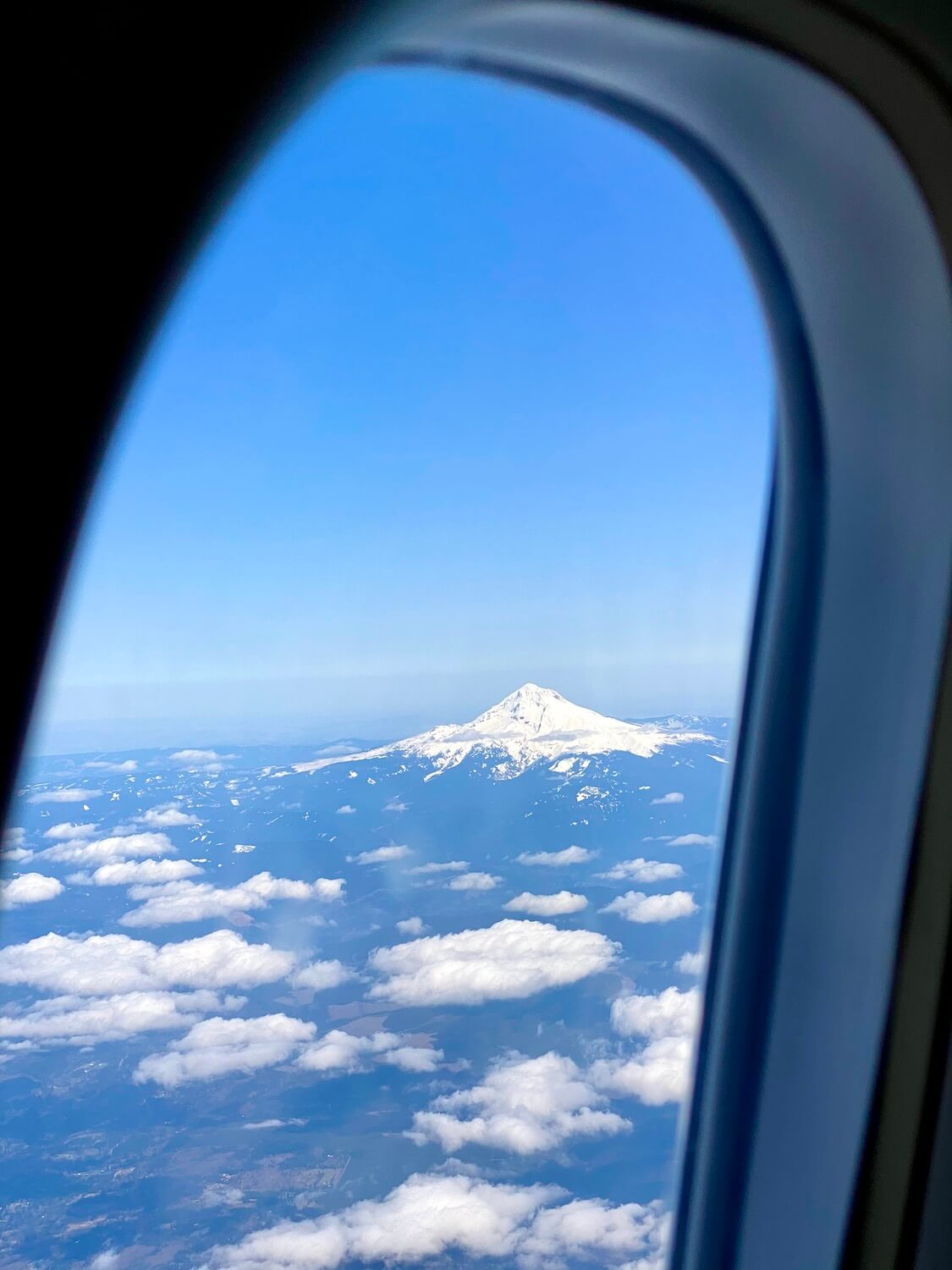 The view out of an airplane window highlights the symmetrical shape of the snow covered peak of Mt. Hood on an airplane flight to Central Oregon.