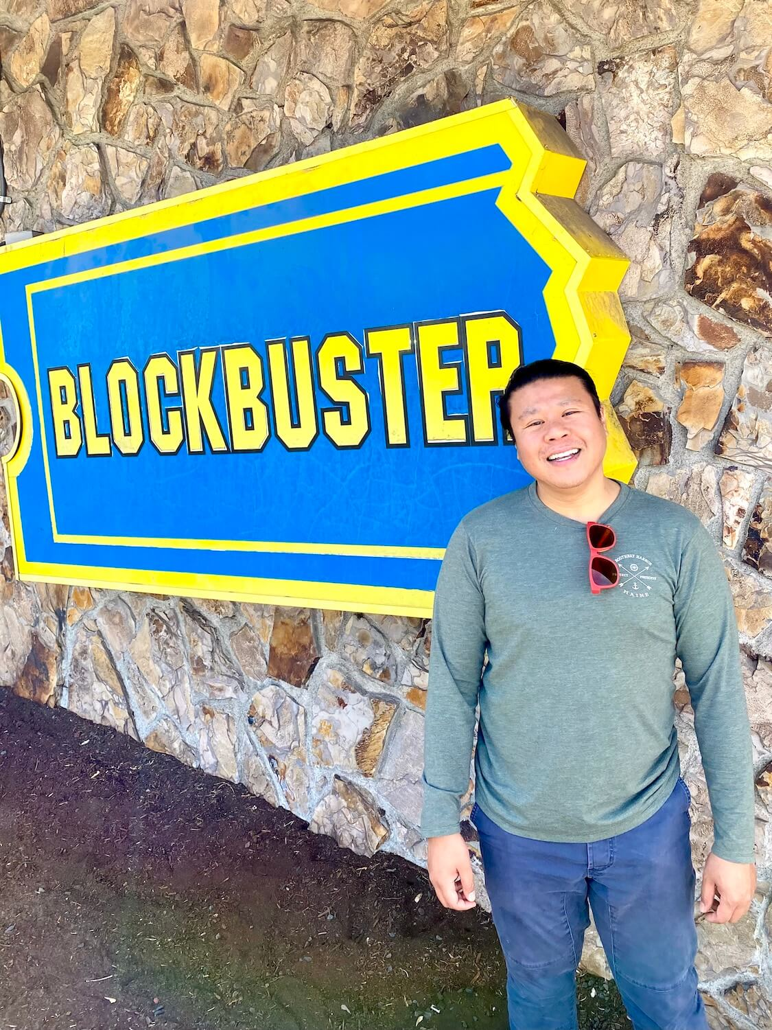 A fun thing to do in Bend Oregon is visit the last Blockbuster Video still in operation.  Here, a man stands in front of the large logo on the front of the rock patchwork wall holding the giant blue sign with yellow highlights.