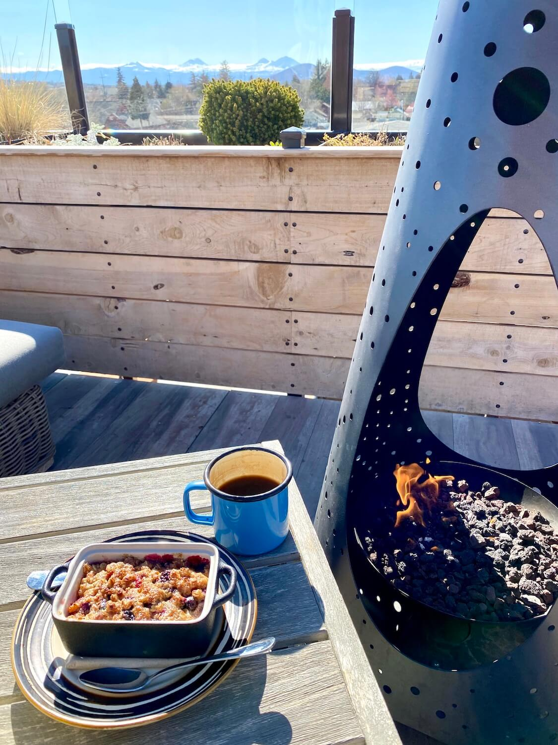 The rooftop bar of the SCP Hotel Redmond offers views of the Cascade Mountains.  On a small slatted table sits a metal cup with coffee as well as a individual sized blueberry cobbler next to an upright firepit with a few flames burning.