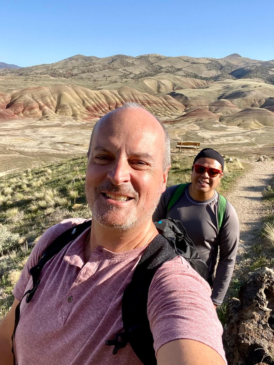 A selfie of Matthew Kessi and his friend Mike while hiking up to the summit of Carroll Rim Trail.  In the background the stunning Painted Range brightens up the horizon with rows of rolling folds and diagonal lines of red swirls.  The Painted Hills in Oregon are fatalistic place to visit.