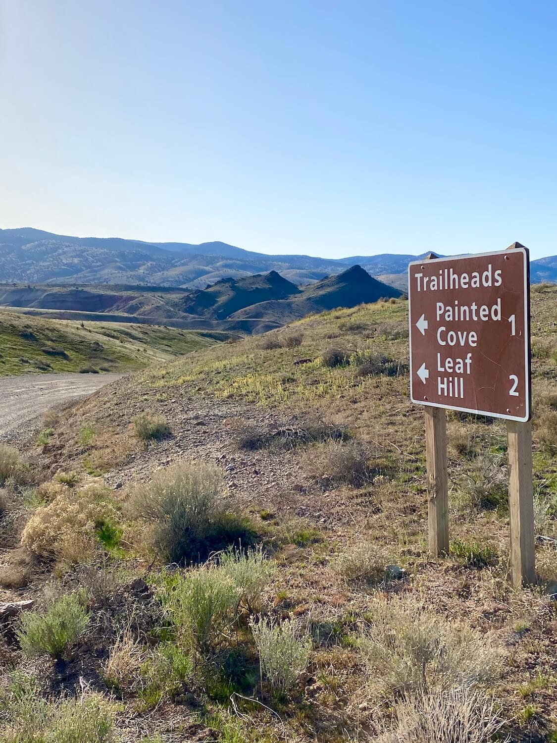 A brown park sign with white lettering indicates the direction to Painted Cove and Leaf Hill, both trails in the Painted Hills monument.  A gravel road runs through the left side of the photo in front of rolling hills covered with low green brush.