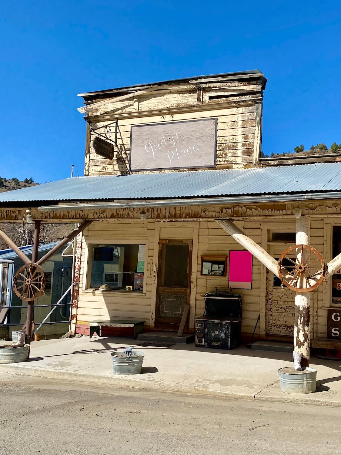 An antique store in Mitchell, Oregon named Judy's Place shows off a western style store front that could be from the pioneer days.  Two old wagon wheels are propped up on the support beams and a bright pink sign is posted near the door.