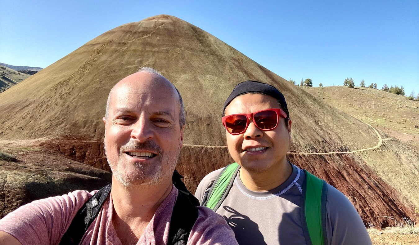 A selfie of Matthew Kessi and his friend Mike in front of a anthill shaped  hill of yellowish soil with reddish hues towards the base of the mound. The sky above is blue with a few trees popping up on the horizon of the hill in the background.