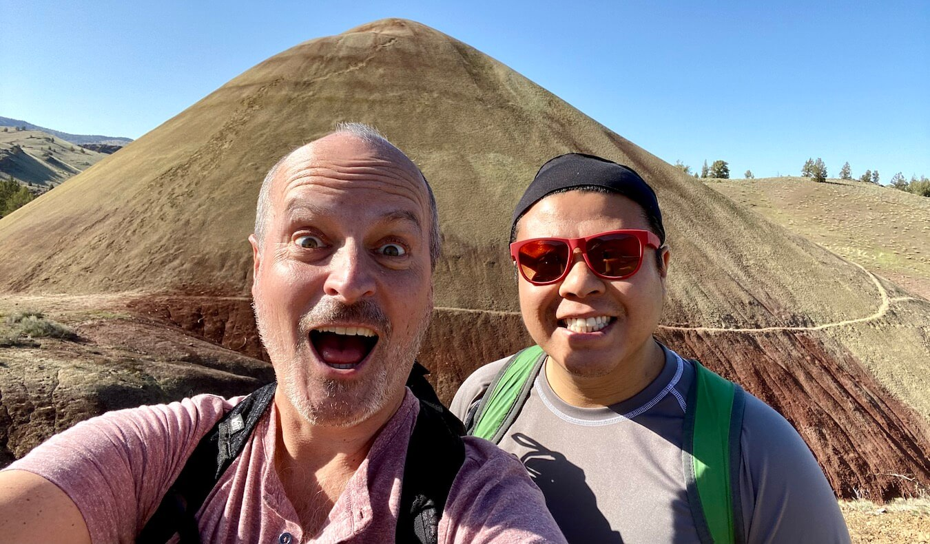 A selfie of Matthew Kessi and his friend Mike making funny faces in front of a anthill shaped  hill of yellowish soil with reddish hues towards the base of the mound. The sky above is blue with a few trees popping up on the horizon of the hill in the background.