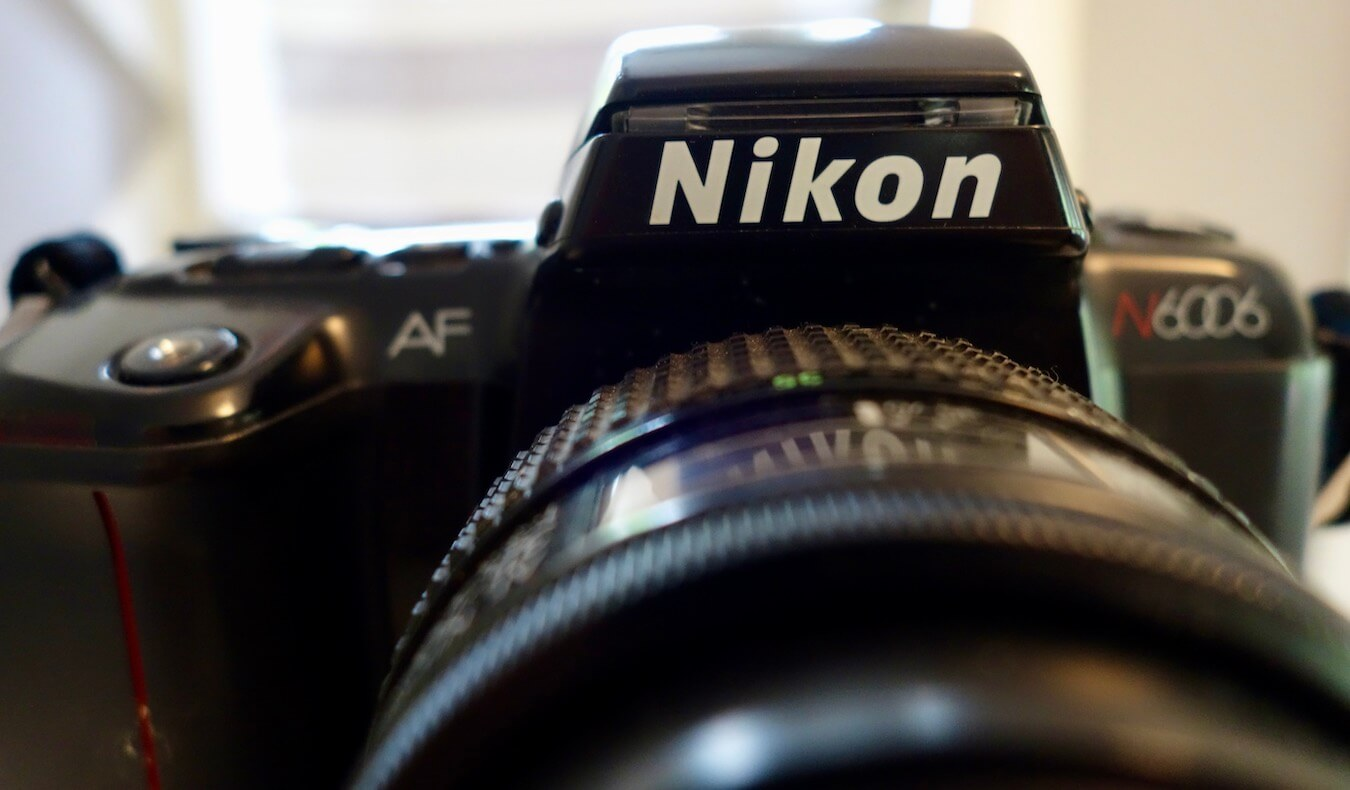 The Photo Gallery of Kessi World has many past cameras, including this Nikon N6006 SLR film camera from the late 1990's.  The NIKON letters are prominent in the shot, with black casing and features.