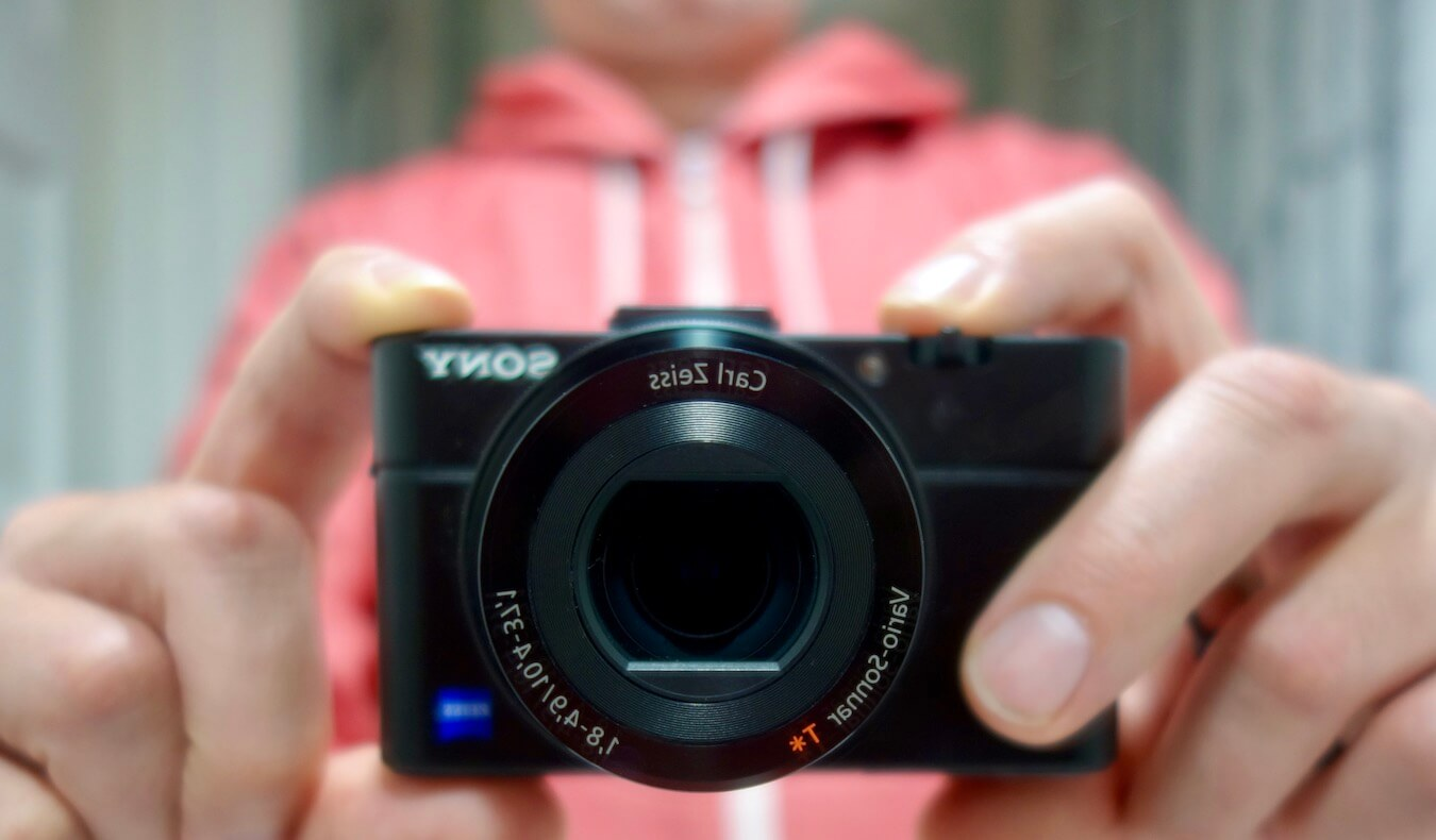 A current camera used by Matthew Kessi is being held up against a bathroom mirror as he stands behind wearing a red hoodie.  His fingers hold the camera, which is a compact black casing.
