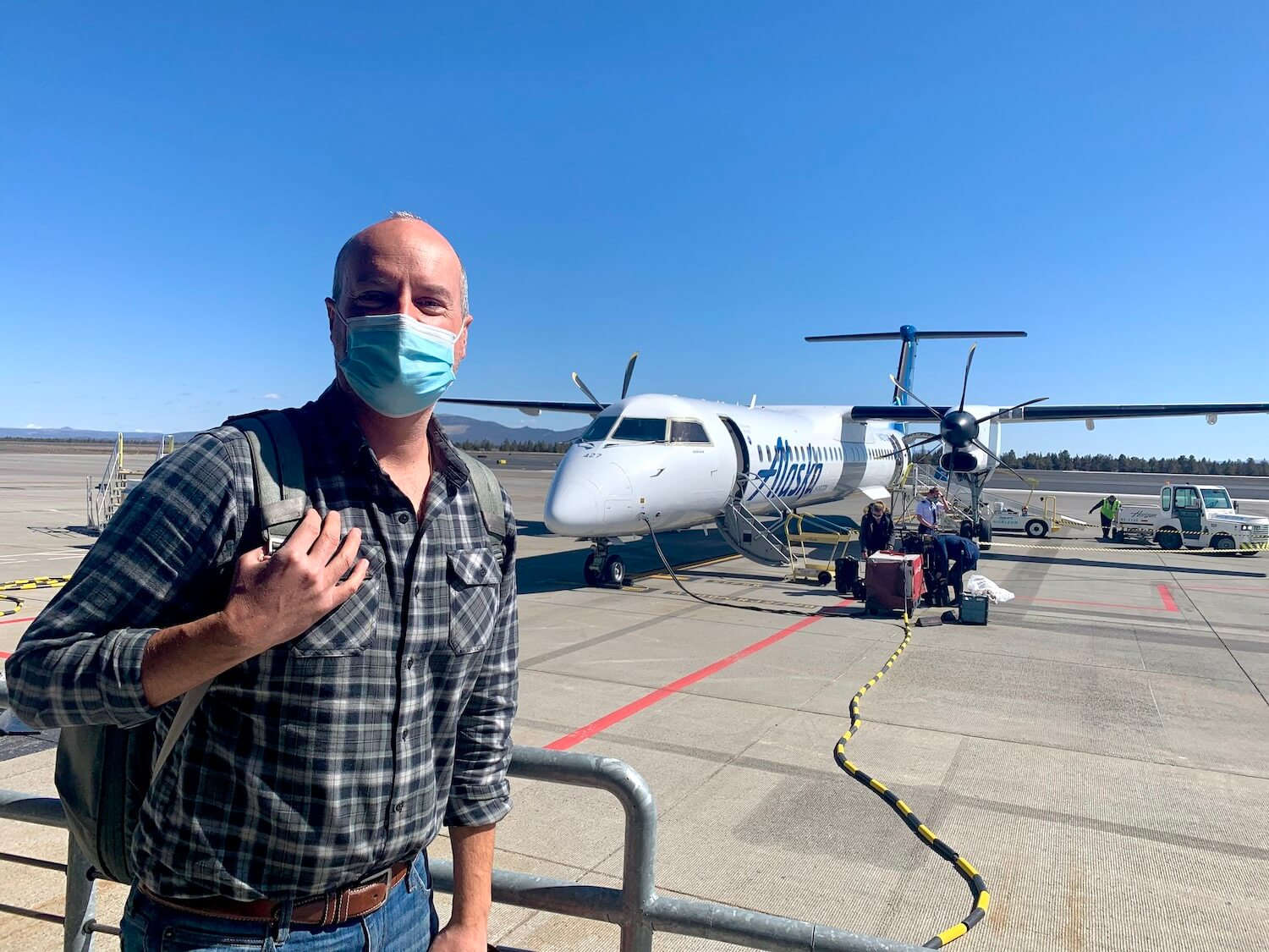 Matthew Kessi deplanes from his Alaska Airlines flight after using frequent flyer miles to fly to Redmond/Bend Airport for a quick getaway. He's wearing a face mask and carrying a backpack.