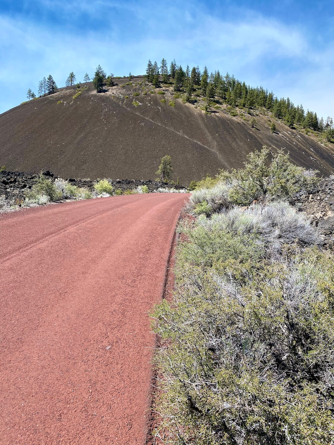 The red paved roadway leading up to the Lava Butte volcano near Bend Oregon is a great thing to do to get out in nature.  The mound is made up of black lava cinders with a number of pine trees growing around the rim.