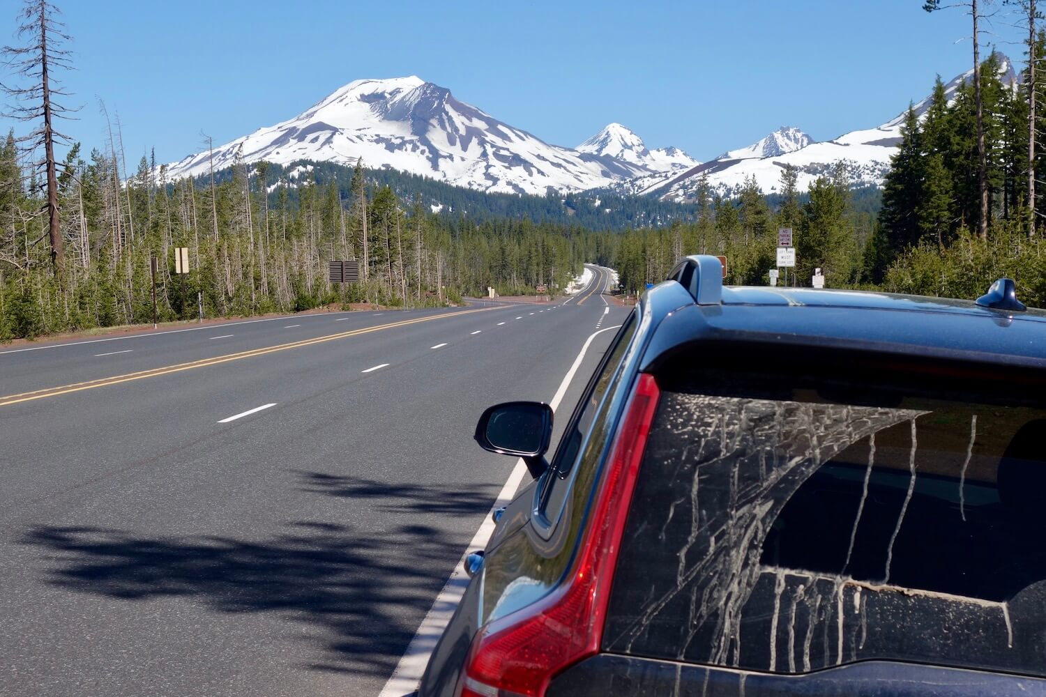 A blue SUV is parked on the side of a highway on an Oregon road trip while the South Sister of the Cascade Mountains rises up snow-covered, toward the blue sky.