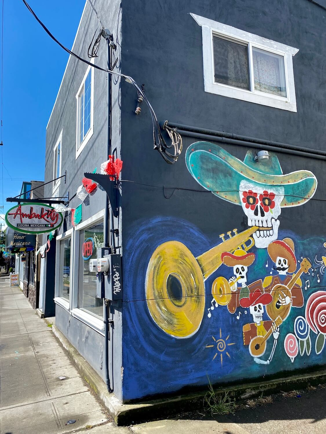 The side of a Mexican restaurant highlights a sugar skull wearing a sombrero playing a trumpet while the rest of the band, in smaller figures also play their instruments.  The rest of the building in the photo is the front of the restaurant, with a basic grey sidewalk and other signs in Spanish on the block in the South Park neighborhood of Seattle.