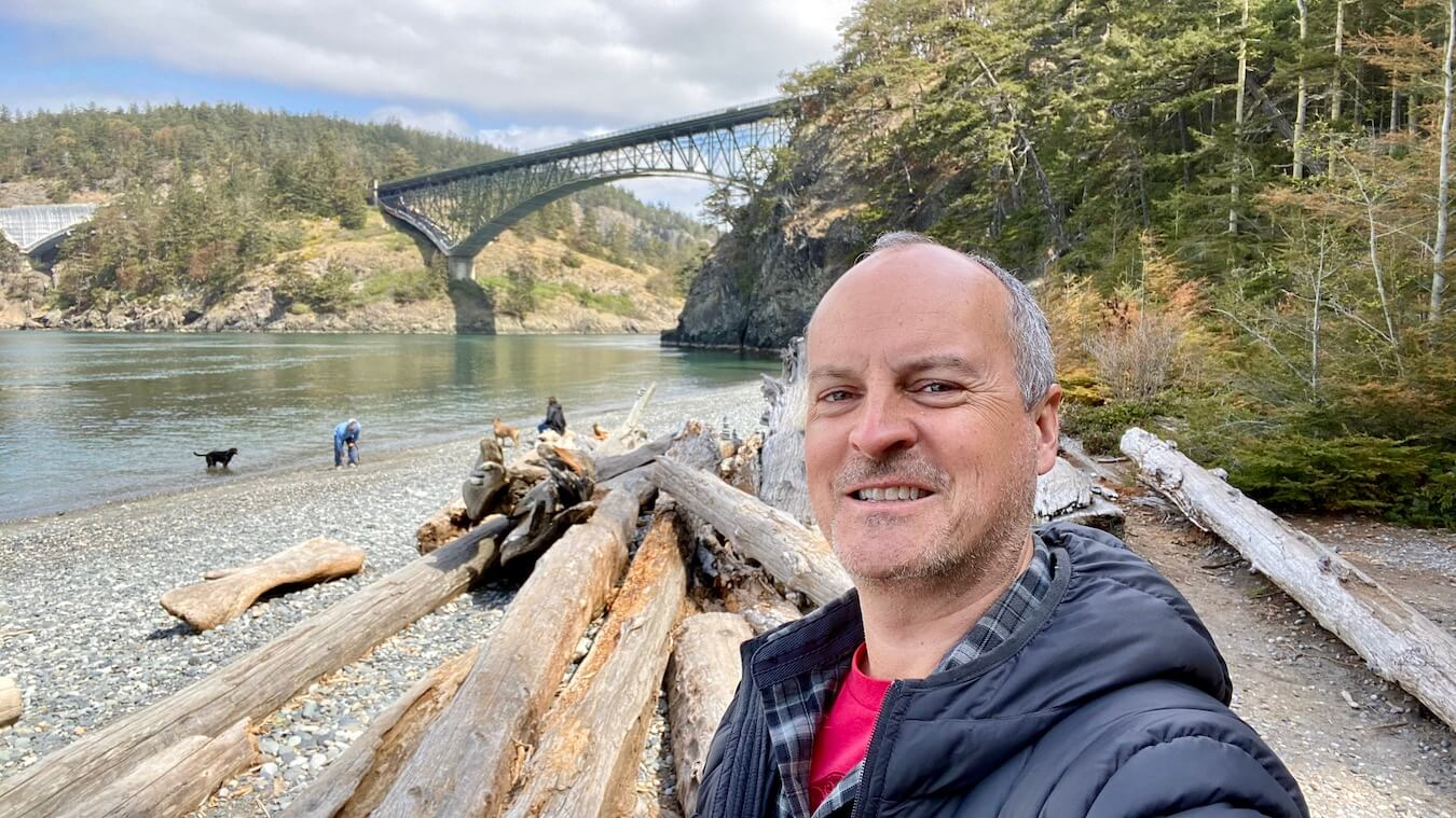 Matthew Kessi takes a selfie underneath the Deception Pass Bridge on Whidbey Island. He's smiling and wearing a red t-shirt with a gray jacket and there are drift logs piled up behind him.