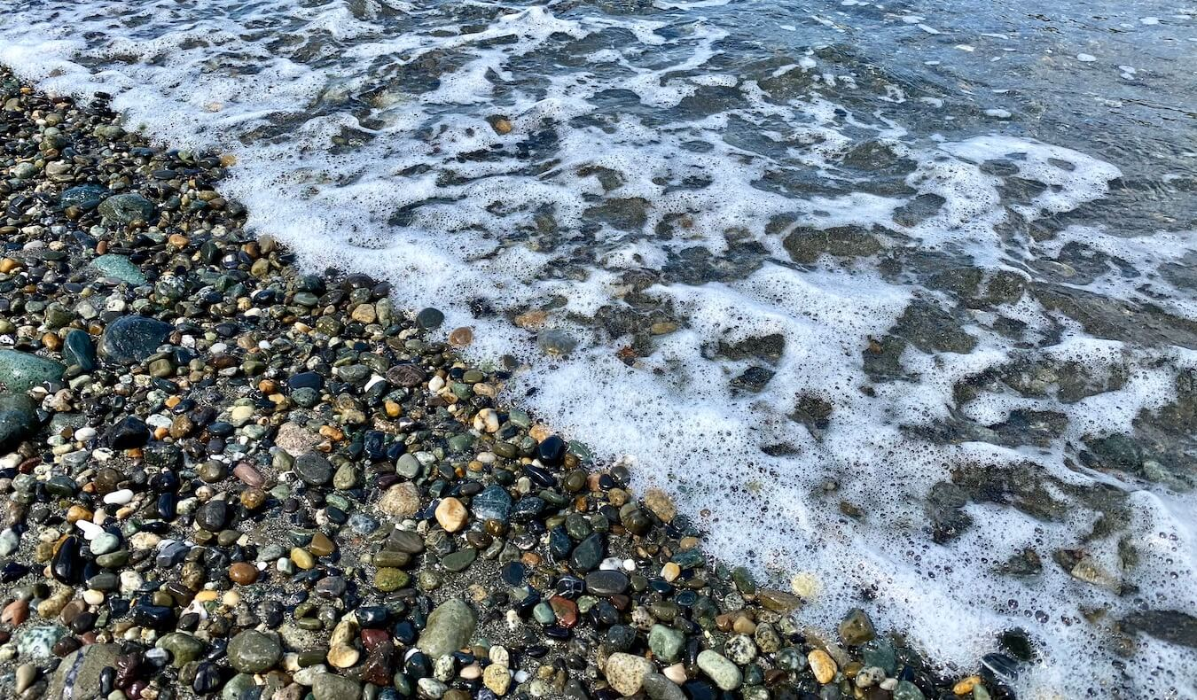 Foamy seawater washes onto a pebble beach.