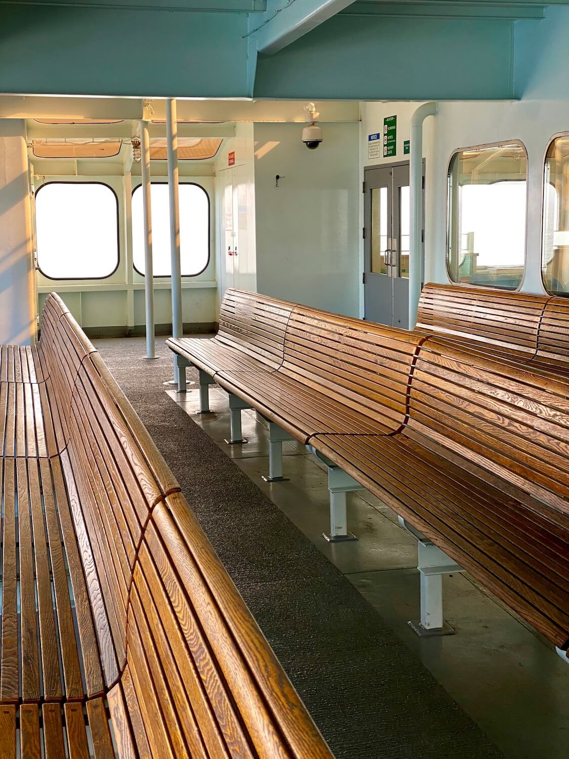 The wooden benches on a Washington State Ferry gently curve to the contour of passengers, but there are none to be seen in this photo.