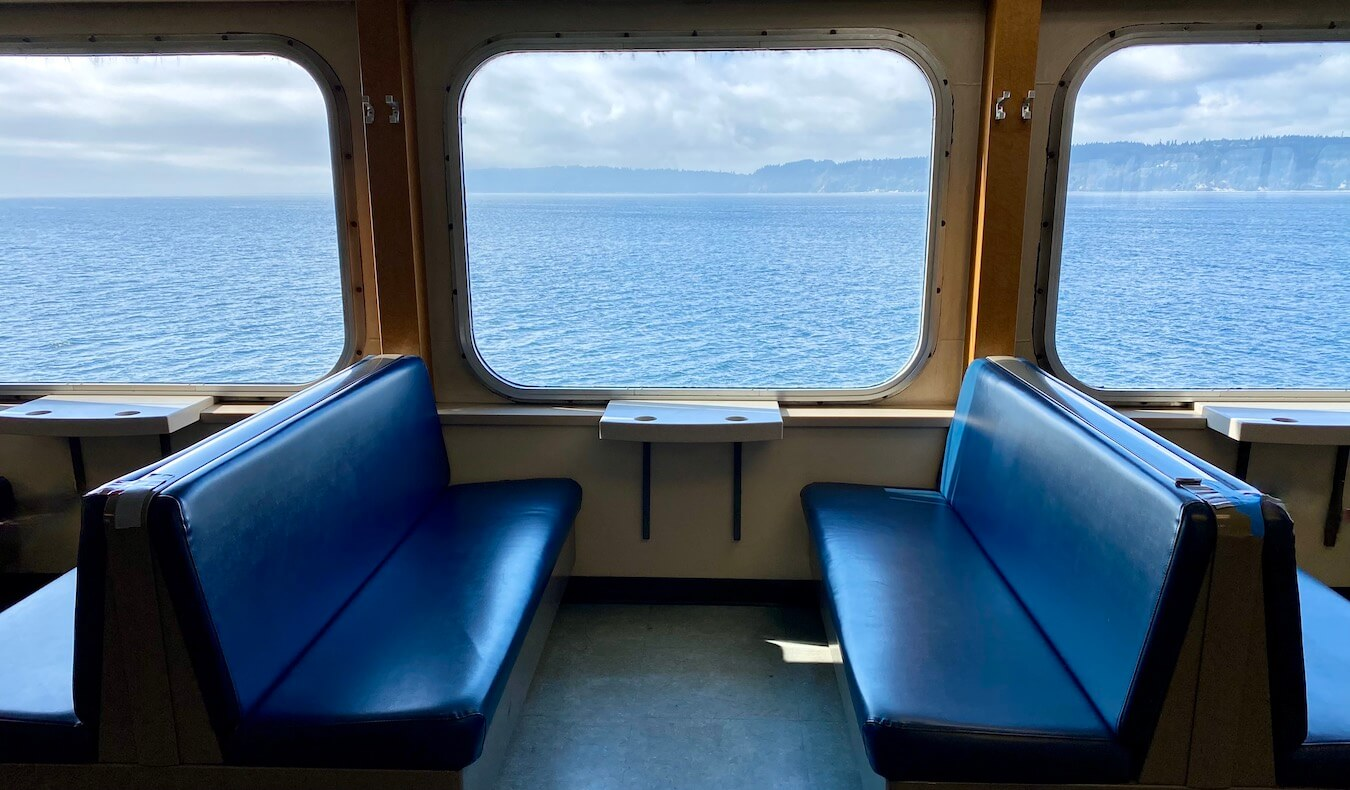 Empty benches on the Washington State Ferry traveling between Mukilteo and Whidbey Island. Outside the windows the blue waters of the Salish Sea ripple while images of land fill the horizon in the distance.