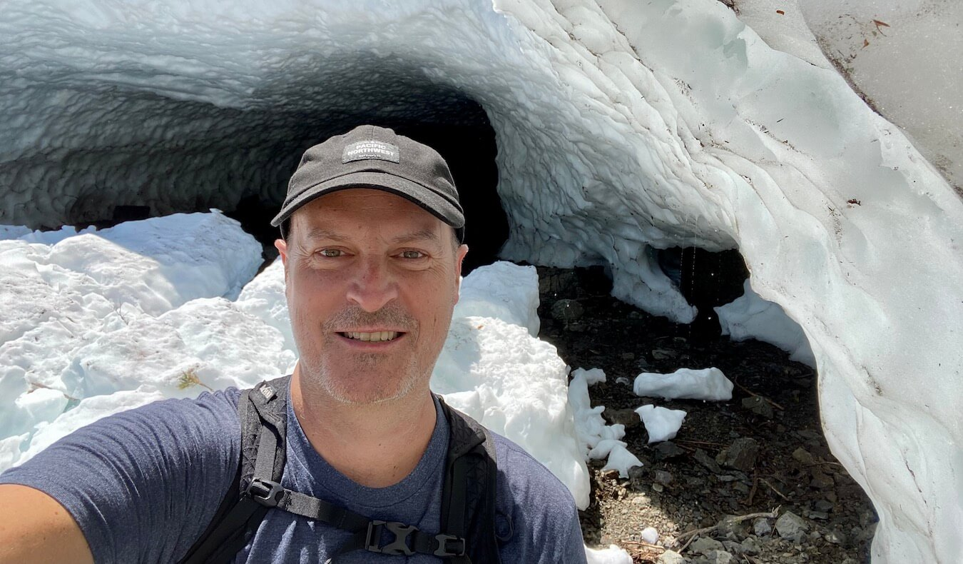 Matthew Kessi poses for a selfie in front of an ice cave at Big Four Ice Caves in the Mt. Baker Snoqualmie National Forest. He's smiling and wearing a black cap and blue t-shirt and the white snow and ice behind him provide a contrast to the photo.