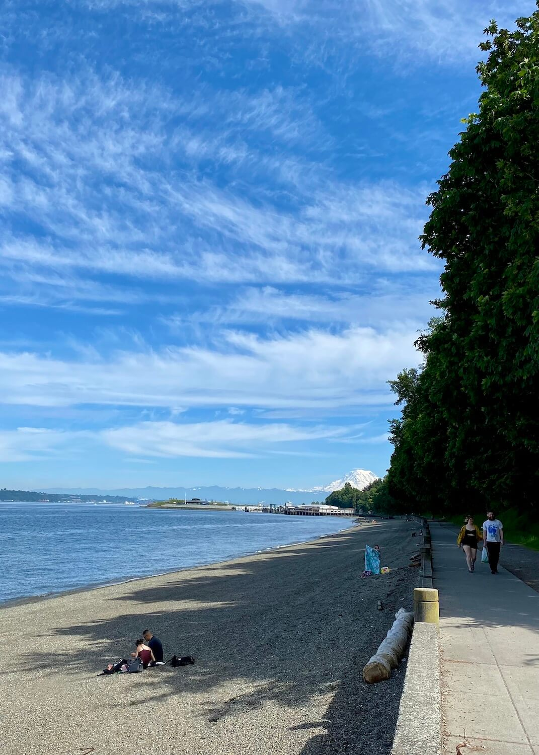 The Promenade at Point Defiance Park is a lovely place to walk along the Salish Sea.  On a nice day like the day this photo was taken Mt. Rainier can be seen in the background.  The tide is low revealing a pebbly rocky beach as two people stroll along the walkway.