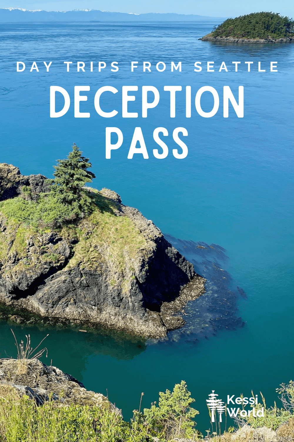 """This Pinterest pin displays white letters that read """"day trips from Seattle"""" and highlights Deception Pass. The snow-covered caps of the Olympic Mountains while a fir-tree covered island is in the middle of the Salish Sea. The foreground shows the rocky costly lined with green grass and moss on the blackish rocks. Kelps sway back and forth in the aqua-green water."""