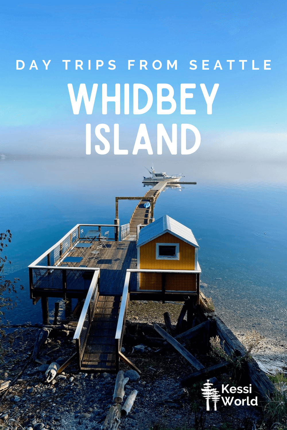 """This Pinterest pin displays white letters that read """"day trips from Seattle"""" and highlights Whidbey Island. The photo shows a boathouse jutting out into Penn Cove with a fishing boat tied to the dock at the end. In the foreground is a bright yellow boat house on a higher dock."""