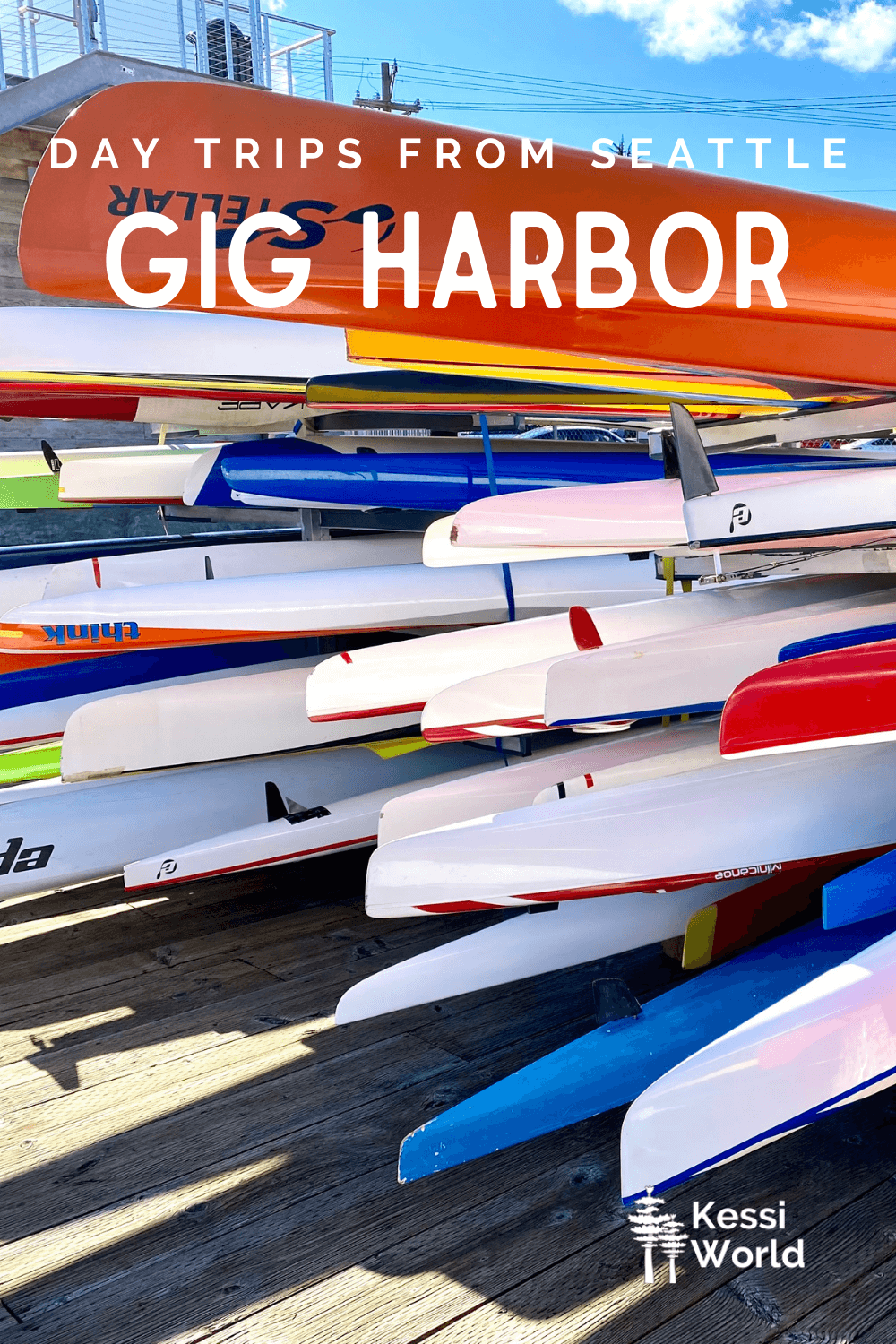 """This Pinterest pin displays white letters that read """"day trips from Seattle"""" and highlights Gig Harbor. The photo shows a storage rack for hundreds of sea kayaks of various colors. The sky above is blue."""