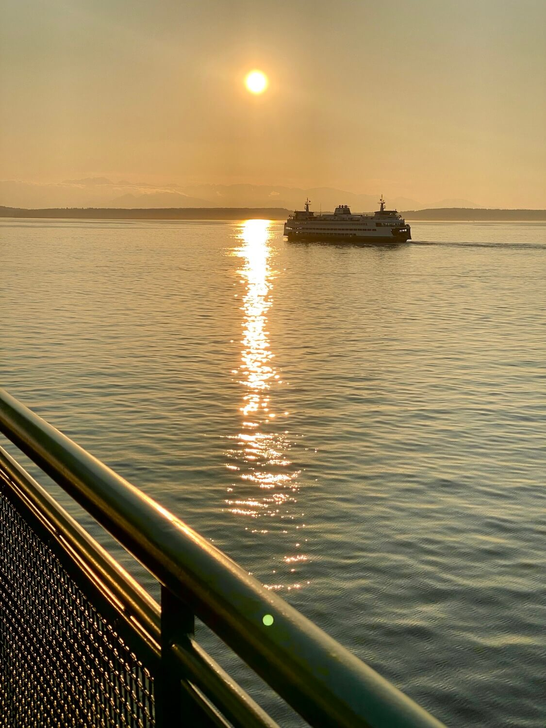 A beautiful golden sunset is captures from the deck of a Washington State Ferry of another ferry in the water. The Olympic Mountains are faint on the horizon while the sun casts a buttery glow on the ripples in the Salish Sea.