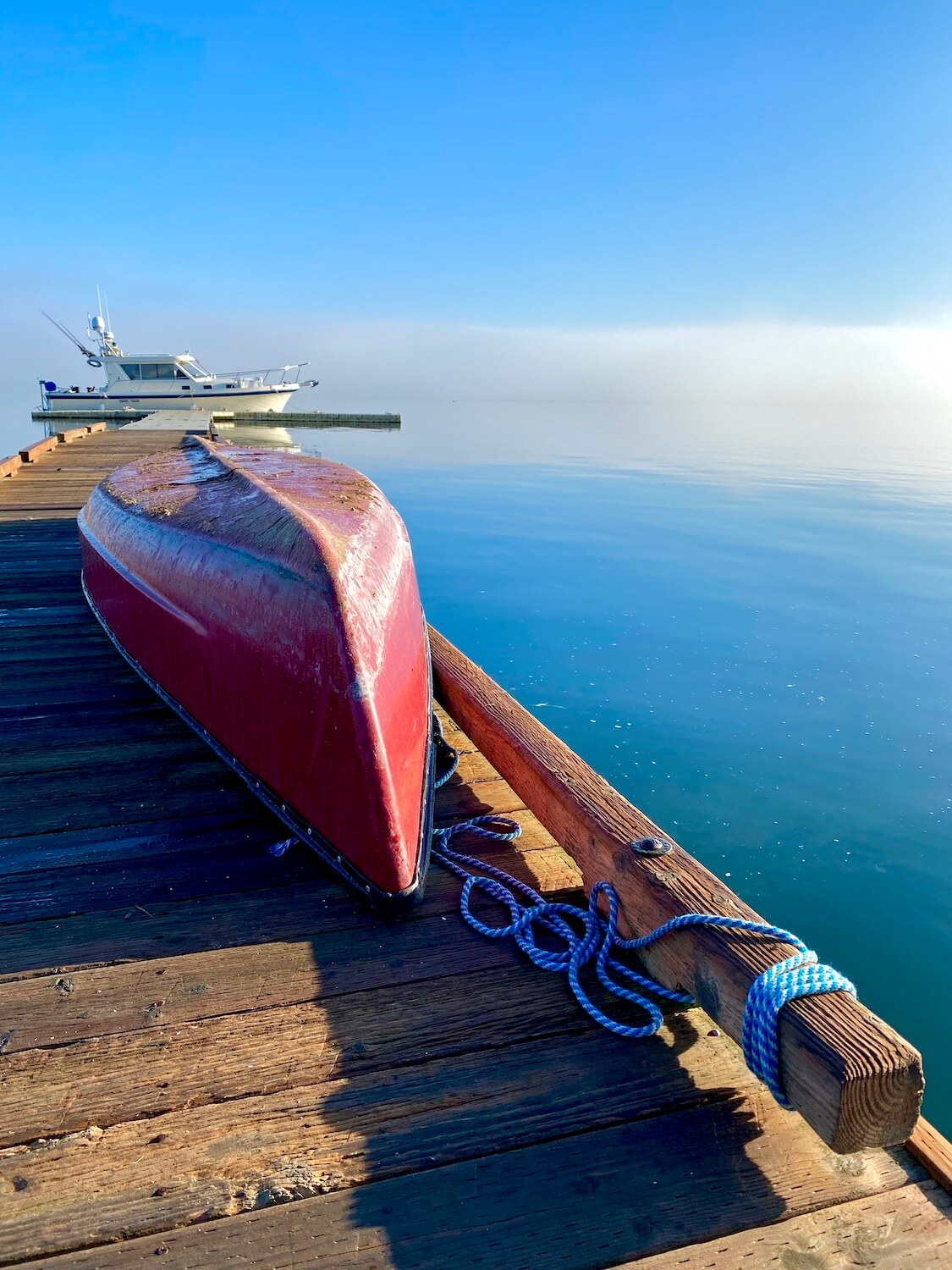 Boating is a popular thing to do on Whidbey Island, and this shot shows an upside down red canoe on a dock with a cruiser fishing boat tied to the dock at the end. The water is blue and fades through some clouds into the horizon.