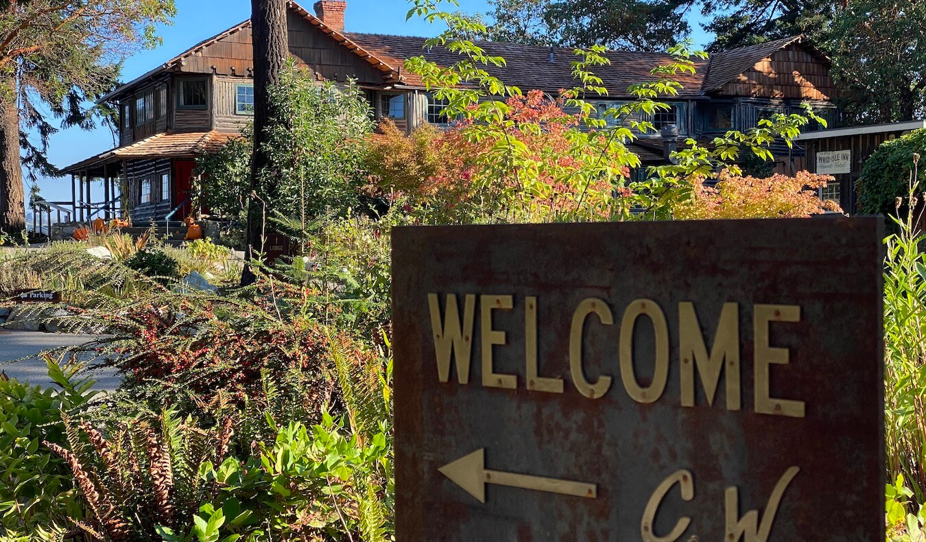 A great thing to do on Whidbey Island is to stay at the Captain Whidbey Lodge. A rusted metal sign welcomes guests with an arrow pointing to the historic lodge, built from wood with cedar shake roof. The sky is blue in the background.
