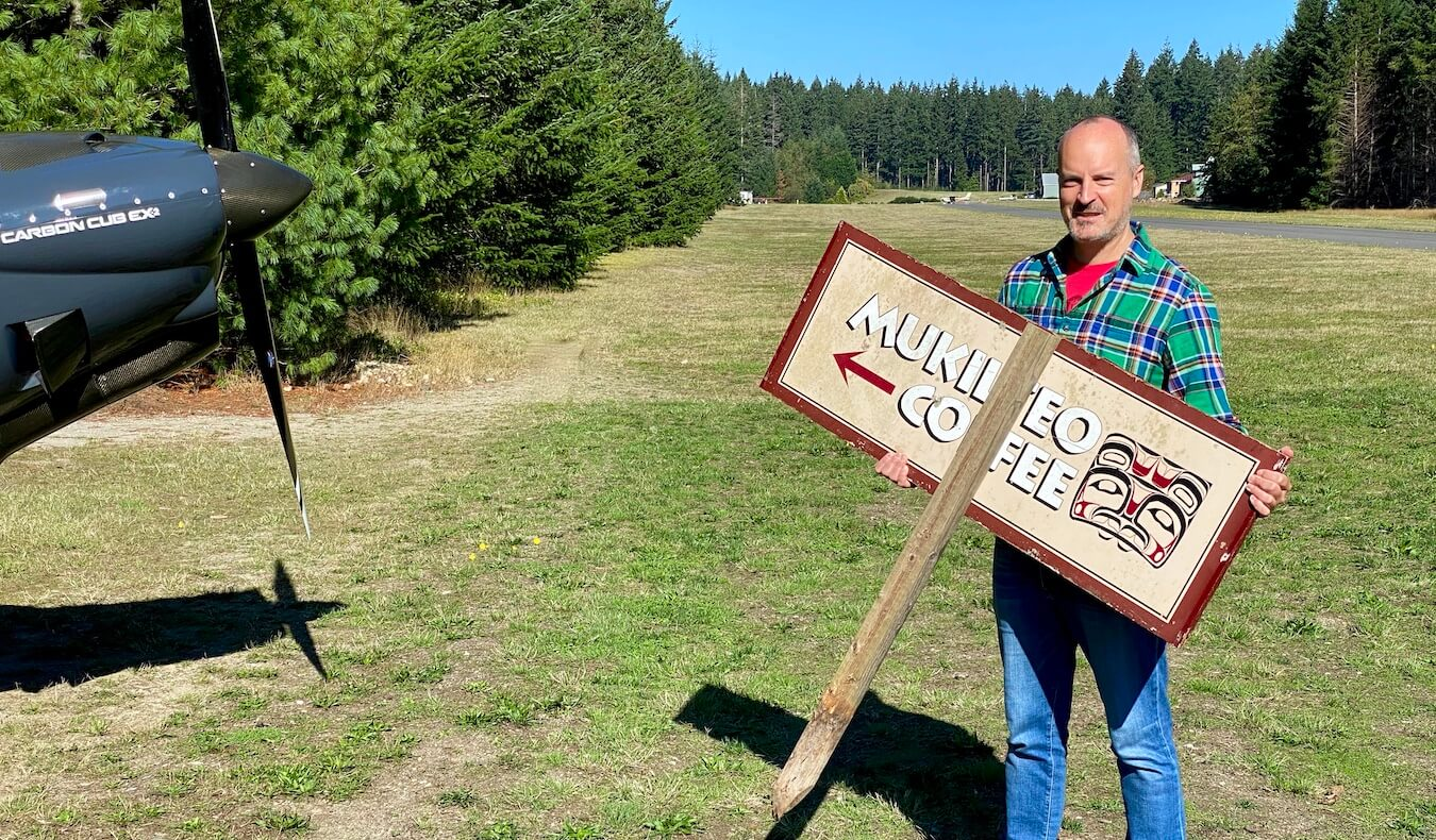 Matthew Kessi stands with a sign for Mukilteo Coffee that has an arrow pointing toward the propeller of a general aviation airplane parked on the side of a landing strip and grass.