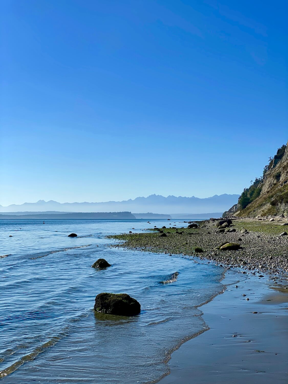 A great thing to do on Whidbey Island is to comb the beach for rocks and shells. This photo shows the beatify of the Olympic Mountains in the background while gentle waves lap up onto the beach which also has a number of small rocks.