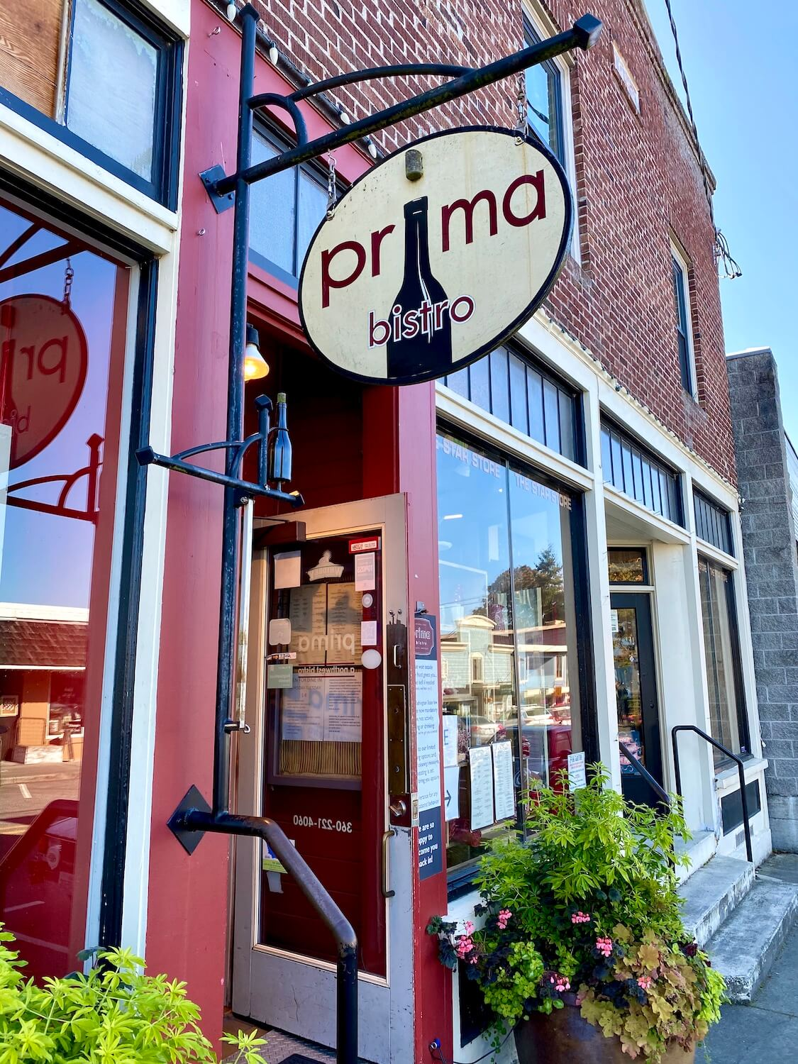 A sign for Prima Bistro hangs from a black metal rod leaning from the red brick building out to the street in Langley, Washington. There is a flower pot with green shrubs and a few flowers.