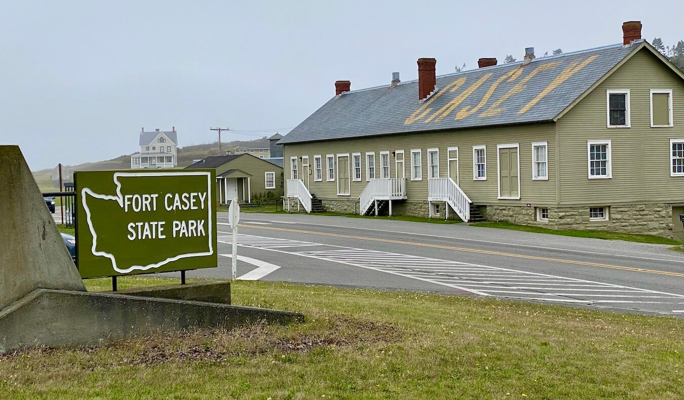 Fort Casey State Park on Whidbey Island is among popular things to do on Whidbey Island. Here the park sign is prominent in white lettering inside the outline of the state of washington, while historic looking buildings fill up the background of the shot.