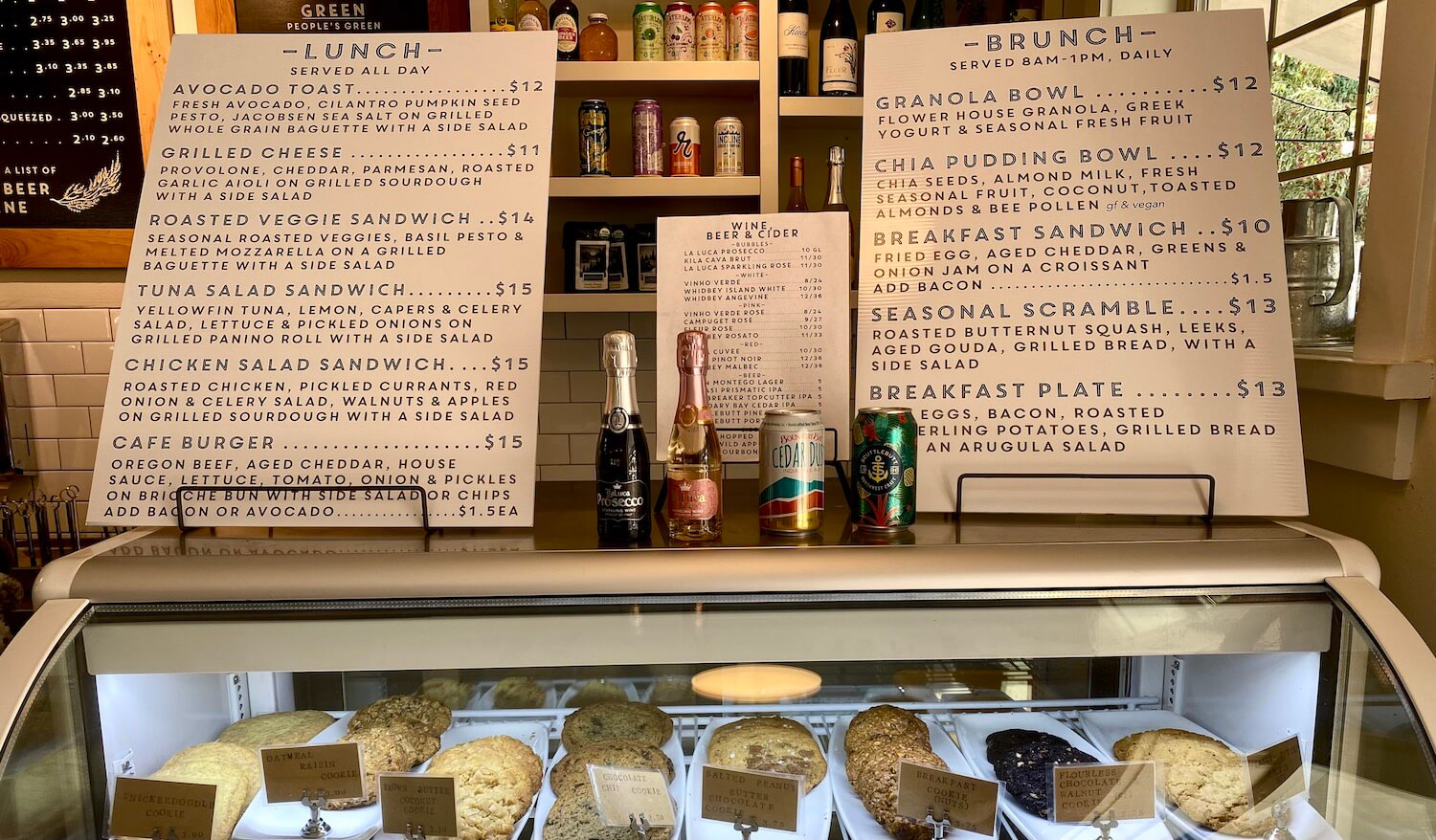 Menus are stacked up on top of a display case with various cookies while the shelves in the back show different beverages available for purchase at this cafe on Whidbey Island.
