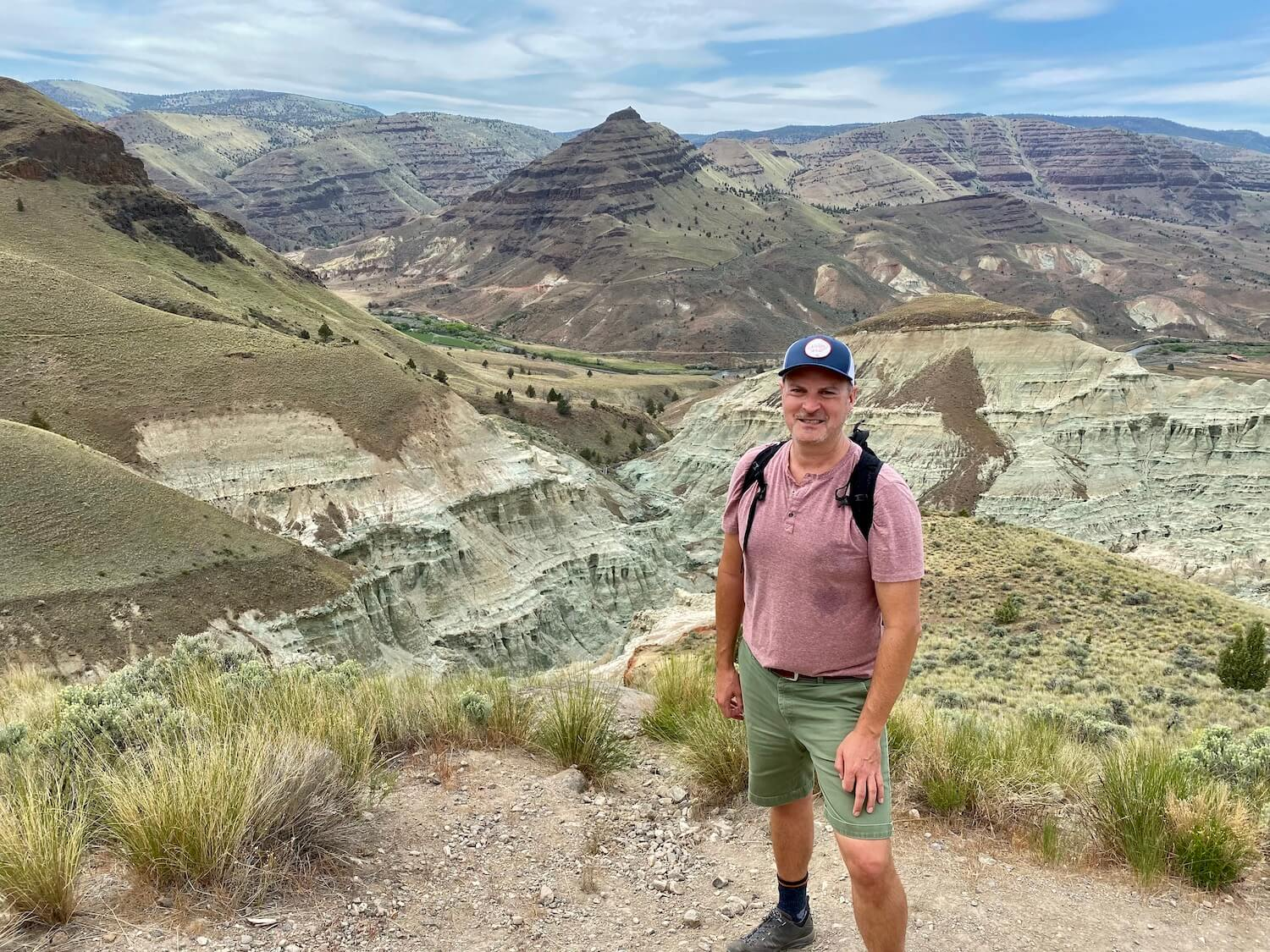 Matthew Kessi poses for a photo at the overlook to the Blue Basin in John Day Fossil Beds National Monument. The canyons are a variety of blue and green colors and continue up to grass covered slopes leading to pointed peaks. There are endless canyons in the background that flow to partly cloudy skies. Matthew is wearing a red shirt and green shorts and a backpack and blue hat. He looks sweaty, as if he is hiking.