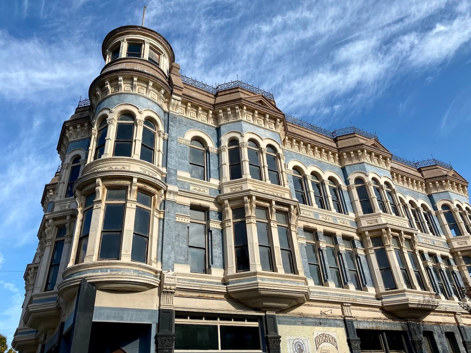 An ornate victorian era building inspires thinking about bygone eras of the seaport town of Port Townsend, Washington. There are so many things to do here, like glance up at this blue and white painted building.